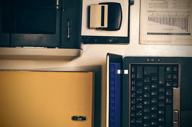 notebook na stole, pohled seshora, vedle tiskárna, razítko a nějaké tiskopisy