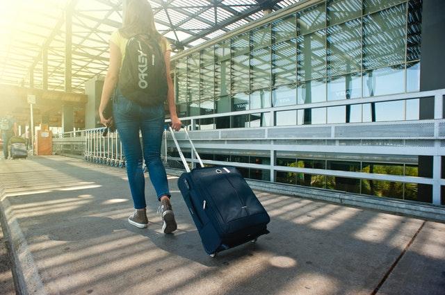 žena s kufrem na chodníku, cestování.jpg