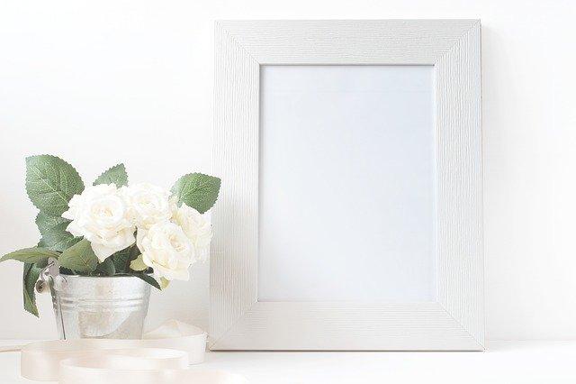 bílá kytice v kyblíku vedle rámečku na obrázek